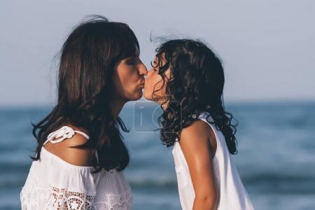 Photo pour Mère et fille s'embrassent sur la plage. - image libre de droit