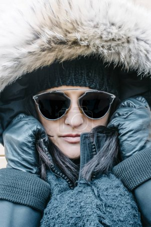 Close-up woman with winter hat, gloves and sunglasses.