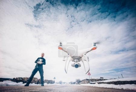 Man flying drone in snowy landscape.