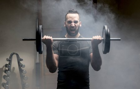 Strong man with beard performs weight training.