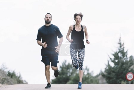 Man and woman play sports and run on the road.