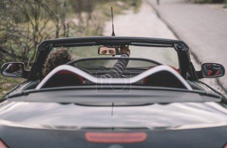 Man inside convertible car placed rear view mirror.