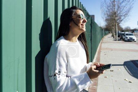 Photo pour Belle femme avec lunettes de soleil et téléphone portable. - image libre de droit