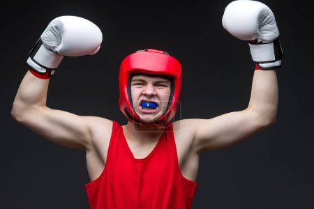 Photo for Teenage boxer in red form and white boxing gloves with hands up. Young champion. Studio shot on black background. - Royalty Free Image
