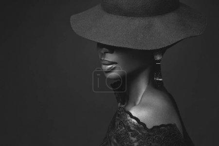 Photo pour Belle jeune femme africaine portant un grand chapeau noir. Portrait de beauté sur fond violet. Espace de copie. Monochrome . - image libre de droit