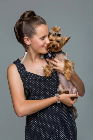 Photo for Beautiful young teenage girl in dress holding small cute yorkshire terrier dog. Copy space. Studio shot on grey background. - Royalty Free Image