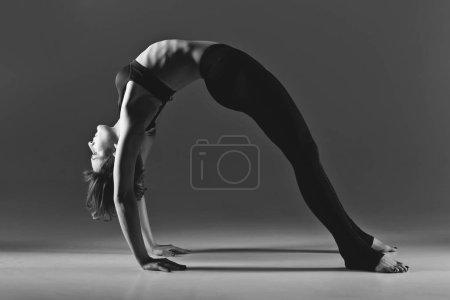 Photo pour Belle jeune danseuse qui s'échauffe. Studio tourné sur fond gris. Espace de copie. monochrome - image libre de droit