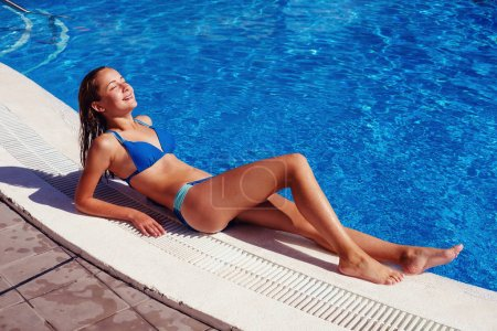 Photo for Beautiful teen age girl sun bathing near outdoor swimming pool. outdoor shot. copy space. - Royalty Free Image