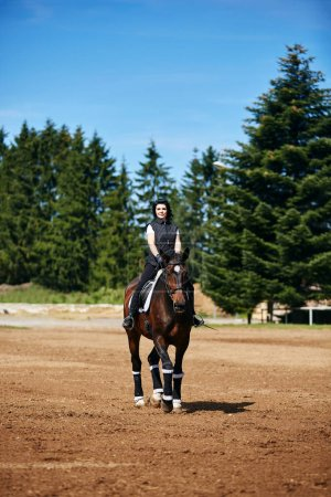Photo for Beautiful young woman riding brown horse in park. outdoor shot. - Royalty Free Image