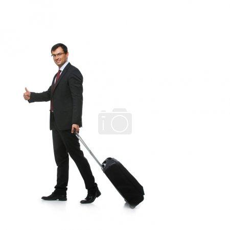 Photo pour Bel homme d'affaires en costume avec valise de voyage isolée sur fond blanc. studio sht. espace de copie . - image libre de droit