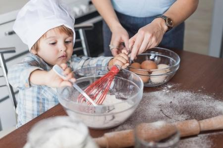 Photo for Mother and child mixing dough for cookies dough at kitchen - Royalty Free Image
