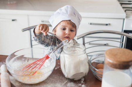 little kid in chef hat preparing dough at kitchen