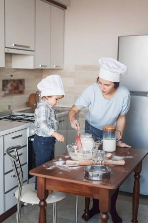 mother and adorable little child mixing dough with whisk at kitchen