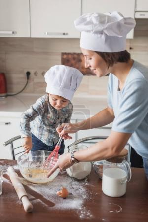 happy young mother and child mixing dough with whisk at kitchen