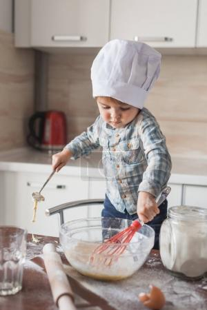 adorable little kid in chef hat mixturing dough with whisk at kitchen