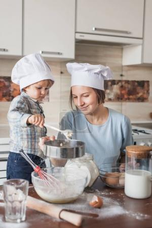 Photo for Mother and adorable child in chef hats preparing dough on messy table at kitchen - Royalty Free Image