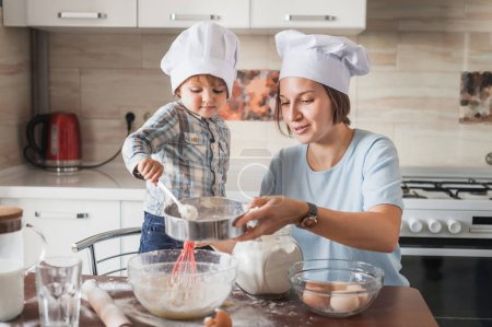 Photo for Happy young mother and child preparing dough for baking at kitchen - Royalty Free Image