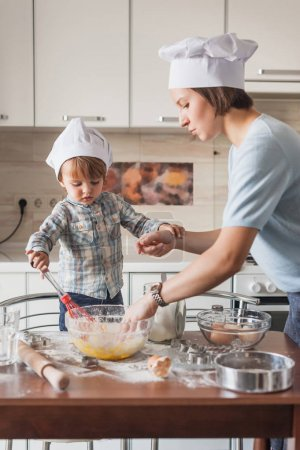 Photo for Mother and child preparing dough for cookies at kitchen - Royalty Free Image