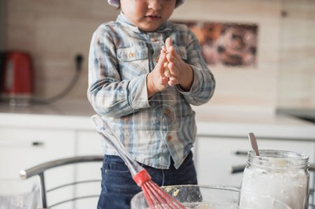 cropped shot of adorable little kid preparing dough at kitchen