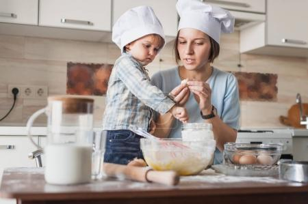 mother teaching her adorable child how to prepare dough at kitchen