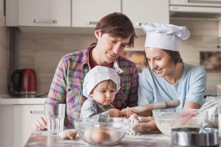 Photo for Happy young family in chef hats preparing cookies at home - Royalty Free Image