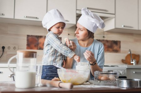 mother teaching her child how to prepare dough at kitchen