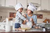 """Постер, картина, фотообои """"Мать учит ребенка готовить тесто на кухне"""""""
