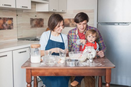 Photo for Young family preparing dough at messy kitchen - Royalty Free Image