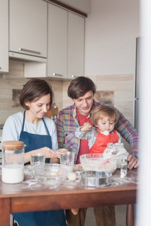 Photo for Happy young family preparing dough at messy kitchen - Royalty Free Image