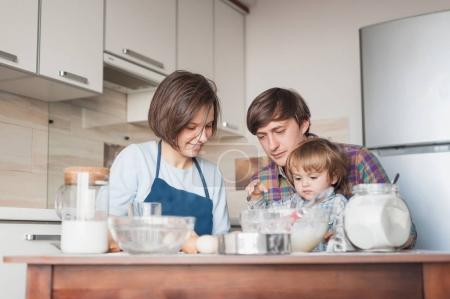 Photo for Beautiful young family preparing dough at kitchen - Royalty Free Image