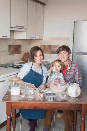 young family preparing cookies in shape of christmas tree