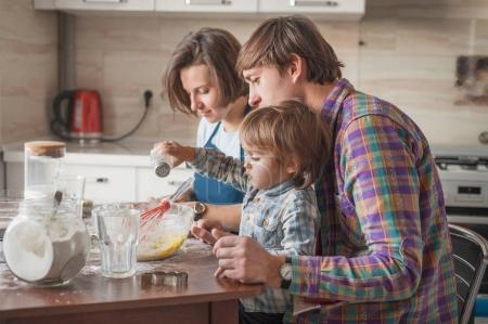 Photo for Beautiful young family making dough at kitchen - Royalty Free Image