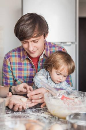 young father and child preparing cookies in shape of heart
