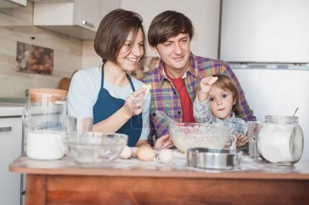 happy young family preparing homemade cookies in shape of hearts