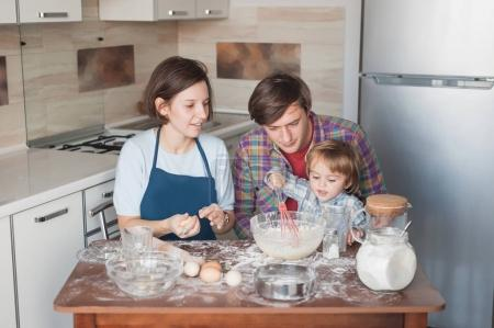 Photo for Beautiful young family preparing homemade cookies in shape of hearts - Royalty Free Image