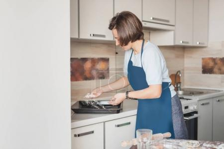 woman spilling flour on baking tray at kitchen to prepare cookies