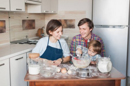 little kid helping his parents with cookies preparation at kitchen
