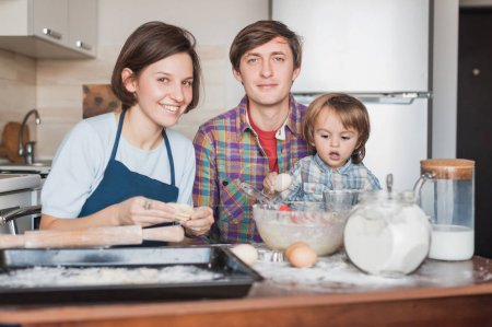 happy family preparing dough for homemade cookies together and looking at camera