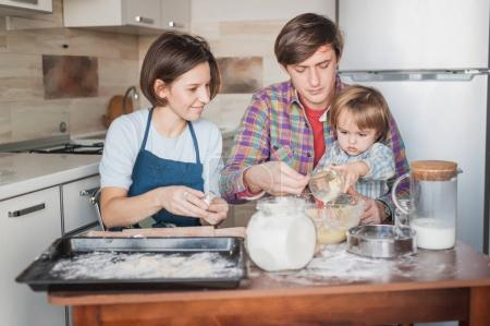 Photo for Young family preparing dough for cookies together - Royalty Free Image