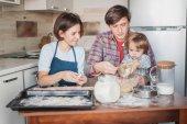 """Постер, картина, фотообои """"Молодая семья готовит тесто для печенья вместе"""""""