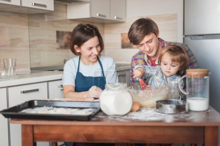 Photo for Beautiful young family preparing dough for cookies together - Royalty Free Image