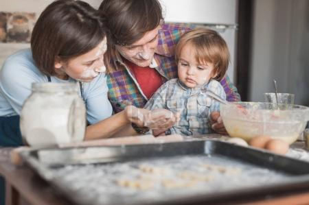 Photo for Beautiful young family preparing cookies together at kitchen - Royalty Free Image
