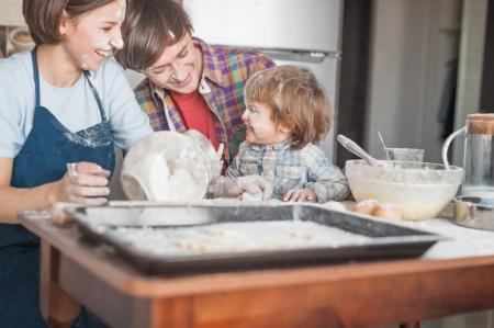 happy young family spilled with flour spending time together at kitchen