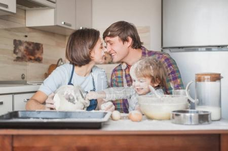 beautiful young family cooking with flour together at kitchen