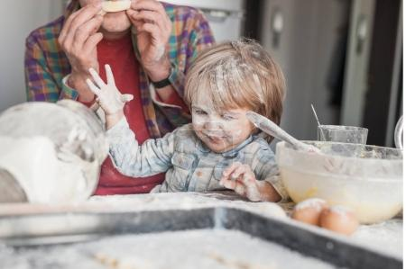 father and child having fun with flour at kitchen