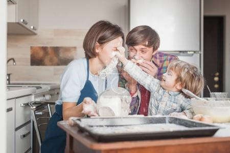 happy young family having fun with flour at kitchen while baking
