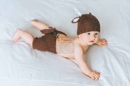 high angle view of infant child in knitted deer costume in bed