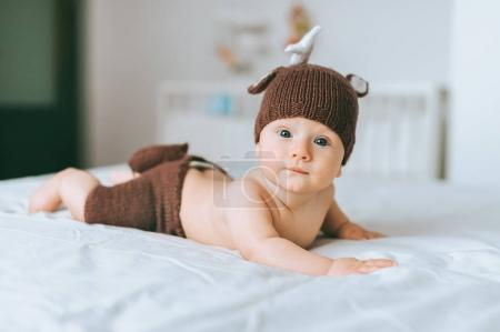 Photo for Infant child in beautiful knitted deer costume looking at camera in bed - Royalty Free Image
