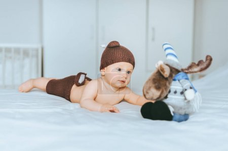 infant child in knitted deer shorts and hat playing with toy moose in bed
