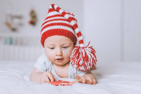 infant child in red and white striped hat looking at toy in bed